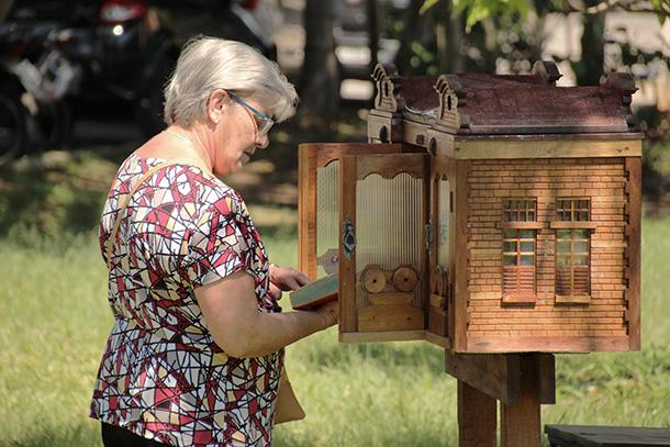 Senhora escolhe livro em Estação de Leitura do município de Tremembé (SP)