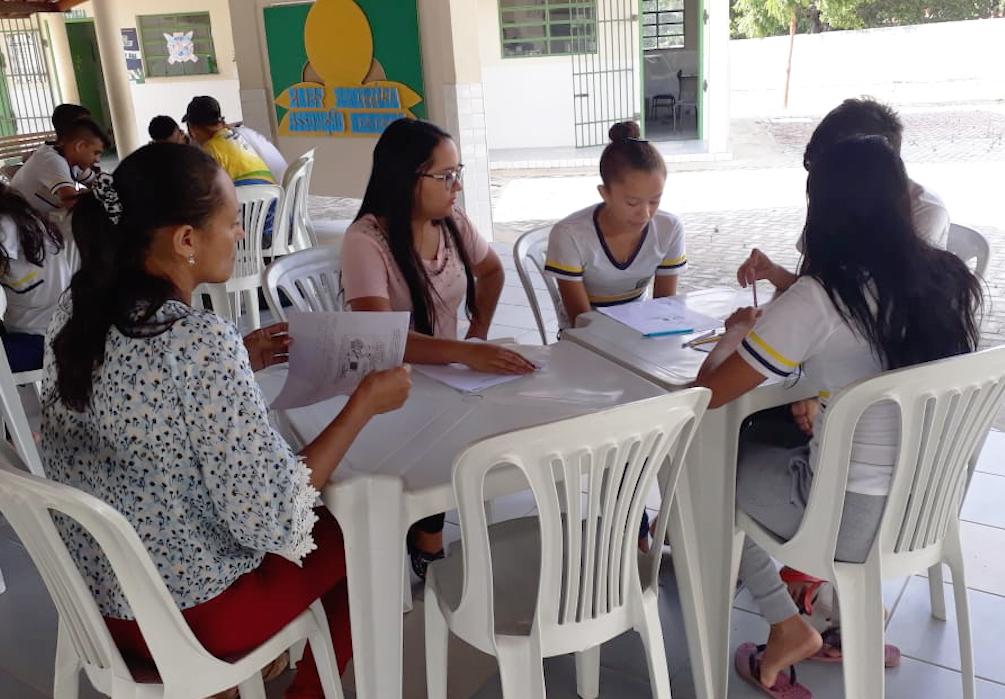 Estudantes e voluntárias estudam juntas durante os Grupos Interativos